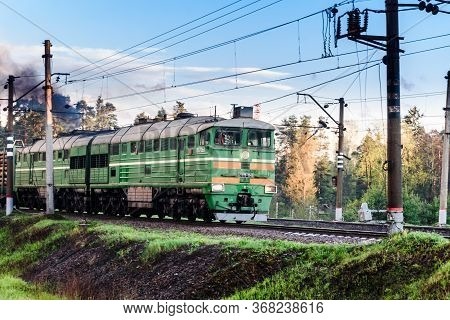 Russia, Gatchina, May 16, 2020: A Freight Train Rides On The Rails. Smoke Billows From The Locomotiv