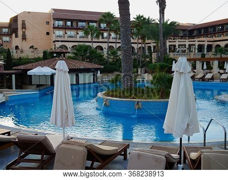 Swimming Pool, Palm Trees And Sunbeds Of A Resort Hotel Paphos, Cyprus - Great And Popular Summer Tr