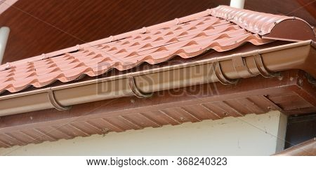 A Close-up On Red Metal Tile Rooftop With Wood Soffit, House Eaves, Rafters And Installed Rain Gutte