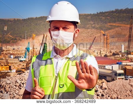 Engineer In Medical Mask Shows Stop Sign Standing Opposite Construction Site