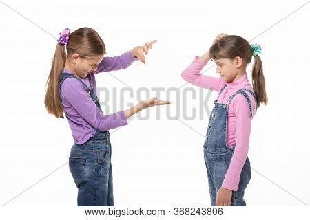 A Girl Shows A Virtual Object On Her Hand, Another Girl Looks At Her And Scratches Her Head In Bewil