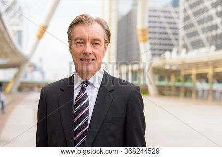 Happy Mature Handsome Businessman In Suit Smiling At Skywalk Bridge In The City