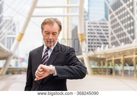 Mature Handsome Businessman In Suit Checking The Time At Skywalk Bridge In The City