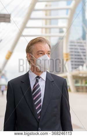 Mature Businessman Thinking With Mask For Protection From Corona Virus Outbreak At Skywalk Bridge