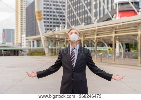 Mature Businessman With Mask Looking Up With Arms Raised At The Skywalk Bridge