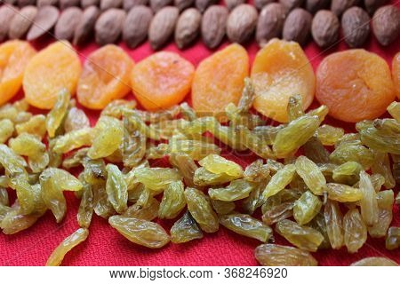 Almonds, Raisins And Dried Apricots Laid Out By A Line On A Red Background. Almonds, Dried Apricots
