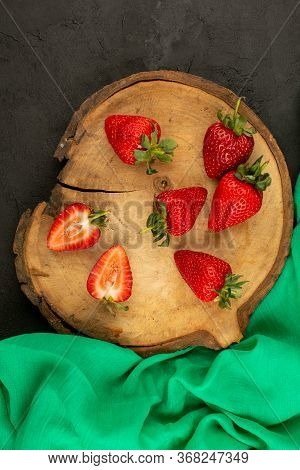 A Top View Sliced Red Strawberries Mellow Ripe On The Brown Wooden Desk And Dark Floor