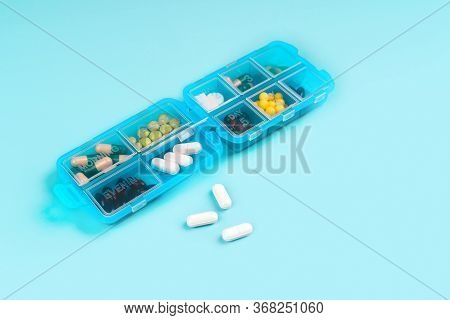 Prescription Pills And Vitamins In A Blue Pill Box On Blue Color Background. Flat Lay Photo, Space F