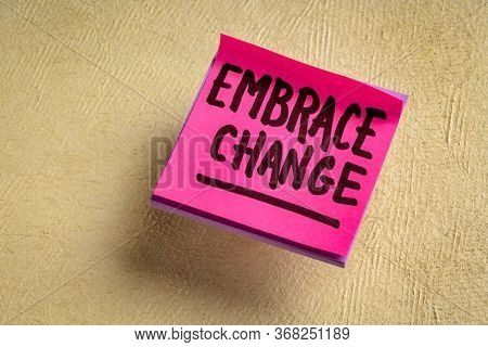 embrace change - handwriting on a  reminder note against textured paper, adaptation in business and personal development