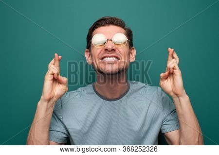 Portrait Of A Tense Young Man With Glasses On A Green Background Who Has Crossed His Fingers And Wor