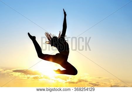 Graceful Gymnast Dancer Jumping Leaps Against Sunset