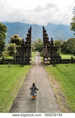 Tourist Woman Walking Through The Balinese Gate Candi Bentar. Vacation On Bali. Aerial View From Dro