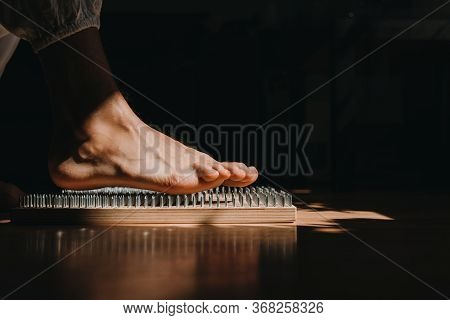 Close-up Of Unrecognizable Brave Man In White Pants Standing Barefeet On Bed Of Nails At Morning Yog