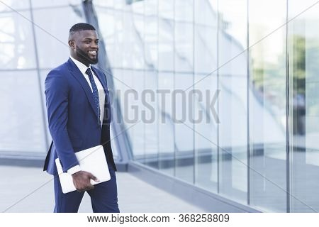 Successful Black Business Man With Digital Tablet Walking In Urban Area Going To Work. Business Peop