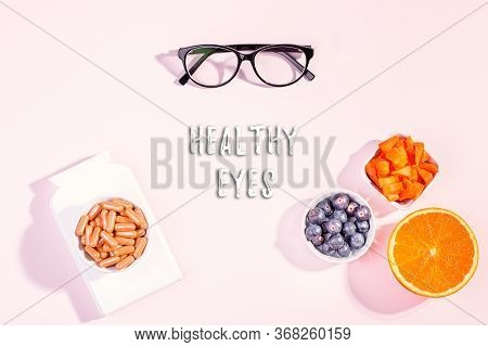 Essential Vitamins And Supplements To Keep Eyes Healthy On Pink Background. Eyeglasses, Vitamin Pill