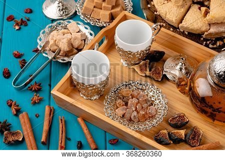 Two Empty Cups On A Wooden Tray With Sugar Cubes And Turkish Baklava On Blue Wooden Table Decorated