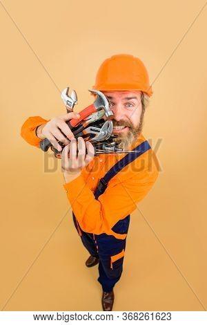 Happy Worker Holds Repair Tools. Building. Builder In Construction Helmet. Repairment Tools. Industr