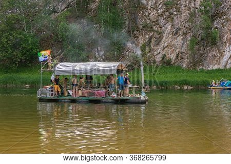 People Relax On Primitive Raft During Rafting On River. Tourists Rafting, Floating. Russia, Bashkort