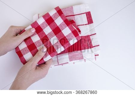 Woman Hands Holding Red Checkered Kitchen Towels. Two Folded Red And White Tablecloth In Female Hand