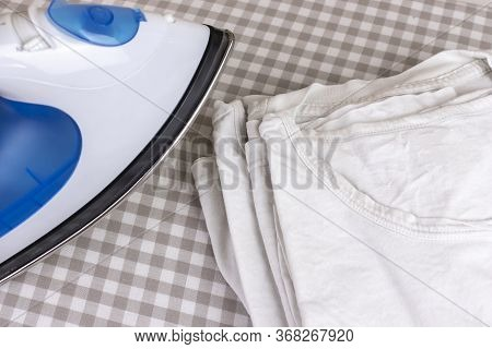 Ironing Stack Of White T-shirts On Board. A Blue Iron And A Pack Of Wrinkled Washed Clean Shirts.
