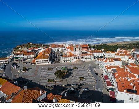 Aerial view of houses and Church of Nossa Senhora da Nazare on the hilltop Nazare, Portugal