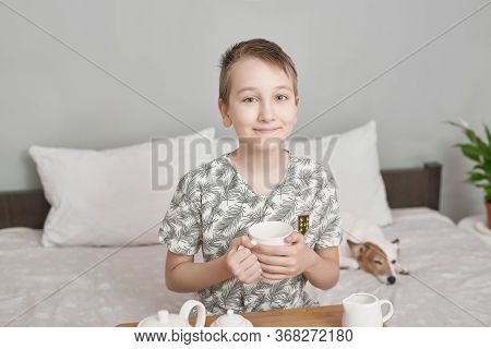 Happy Boy Sitting On Bed And Drink Tea. Empty Space For Text. Friendship Concept. Cute Little Boy Wi