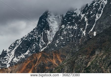 Low Stormy Clouds Touch Top Of Snowy Mountain. Dismal Overcast Awesome Landscape With Big Rocks And