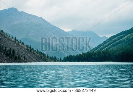 Dramatic View To Vast Mountain Lake Among Giant Mountains In Rainy Weather. Pines And Larches On Hil