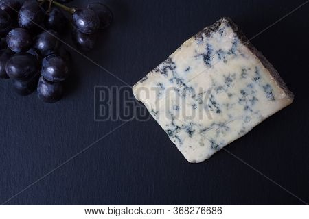 Stilton Blue Cheese With Sable Grapes On A Slate Background