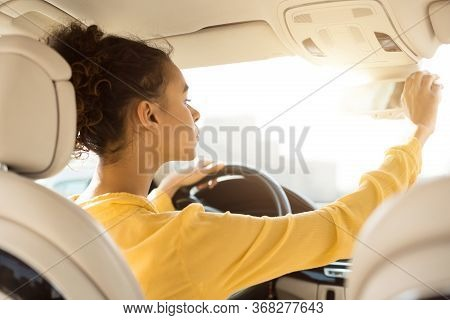 Buying New Car. African Woman Adjusting Mirrors Checking Auto During Test Drive Sitting In Drivers S
