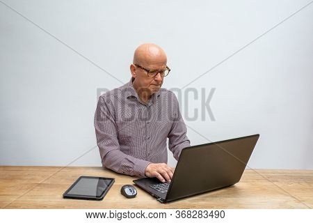 Caucasian Male Middle Aged And With Glasses, Sitting Behind A Desk Working With His Lap Top