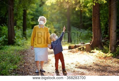 Elderly Grandmother And Little Grandchild Wearing Facemask Walking Together In Sunny Summer Park. Gr