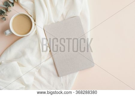 Flat Lay, Top View Home Office Desk Table With Paper Notebook, Blanket And Cup Of Coffee On Beige Ba