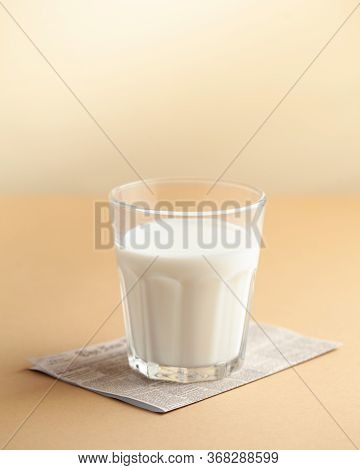 A Glass Of Milk Close-up On A Brown Background. The Concept Of Farm Dairy Products, The Use Of Milk.