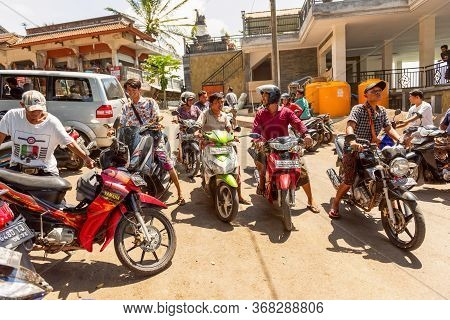 Bali, Indonesia - November 30, 2019: Road Traffic On Bali. Many Motorbikes Wait At The Crossroads. B