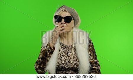 Elderly Style Granny Caucasian Mature Woman In Sunglasses Posing, Smoke Cigarette On Chroma Key Back