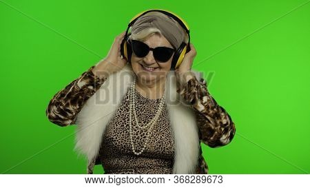 Elderly Style Granny Caucasian Mature Woman In Sunglasses Dancing, Listen Music In Headphones On Chr