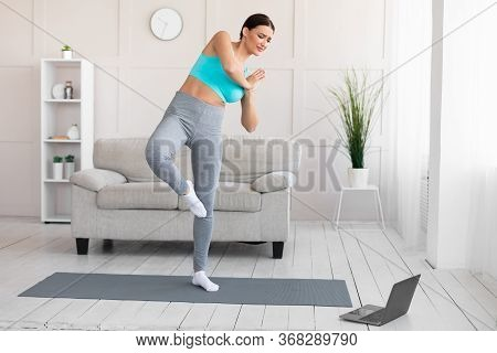 Woman Beginning Practicing Yoga Online Exercising At Laptop Trying To Stand In Vrikshasana Pose At H