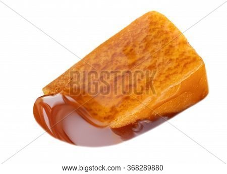 Caramel Isolated On White Background. Caramel Piece With Flowing Toffee Sauce, Top View. Macro