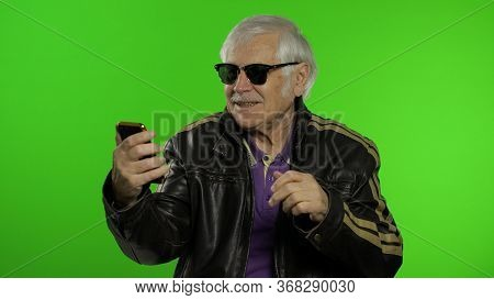 Elderly Stylish Grandfather Caucasian Mature Rocker And Biker Man Using App On Smartphone For Video
