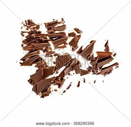 Chocolate Broken Pieces And Shavings Isolated On White Background. Chunks Of Dark Chocolate Falling,