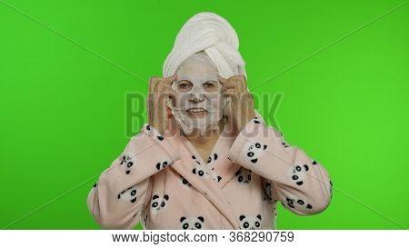 Adult Senior Caucasian Woman Grandmother In Bathrobe And Towel Over Head Applying Cosmetic Fabric Fa