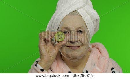 Adult Senior Caucasian Woman Grandmother In Bathrobe Over Head Having Fun With Kiwi While Applying C