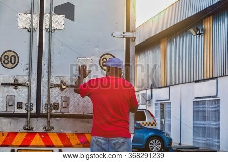 African driver in the back of a truck talking on the phone, checking the load