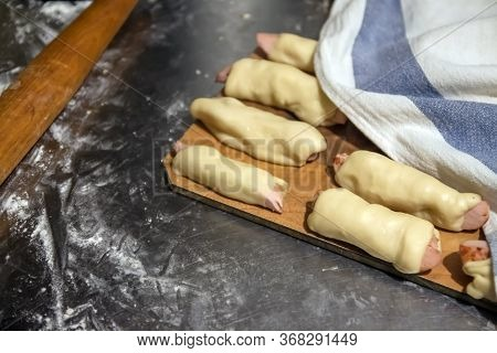 Prepared Raw Sausages In The Test Before Baking Lie On A Table Under A Napkin. Concept, Home Cooking