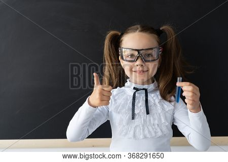 A Modern Schoolgirl At The Blackboard Conducts Experience. In Her Hands Is A Glass Flask With A Blue