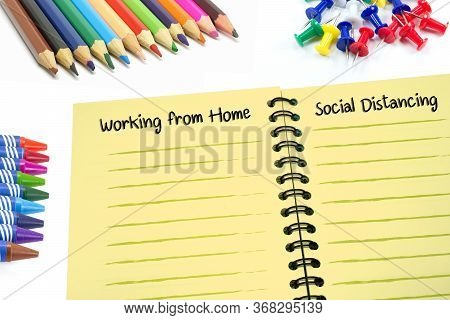 Working From Home And Social Distancing Texts On Notebook With Colorful Supplies On White Background