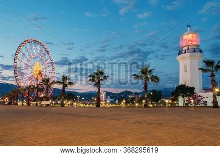 Large Sidewalk With Lighthouse And  Ferris Wheel On A Daybreak With Blue Cloudy Sky Background