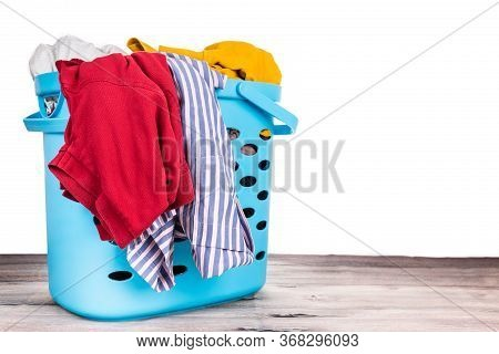 Laundry Basket Full Of Worn Apparels For Washing On Wooden Table