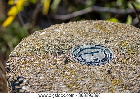 Selective Focus On Metallic Plate On Concrete Pole To Indicate Geodesic Point. Translation Is Nation